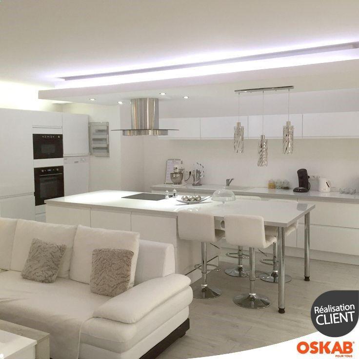 Cuisine tendance et sophistiquée blanche brillante et sans poignée ouverte sur salon pièce totalement