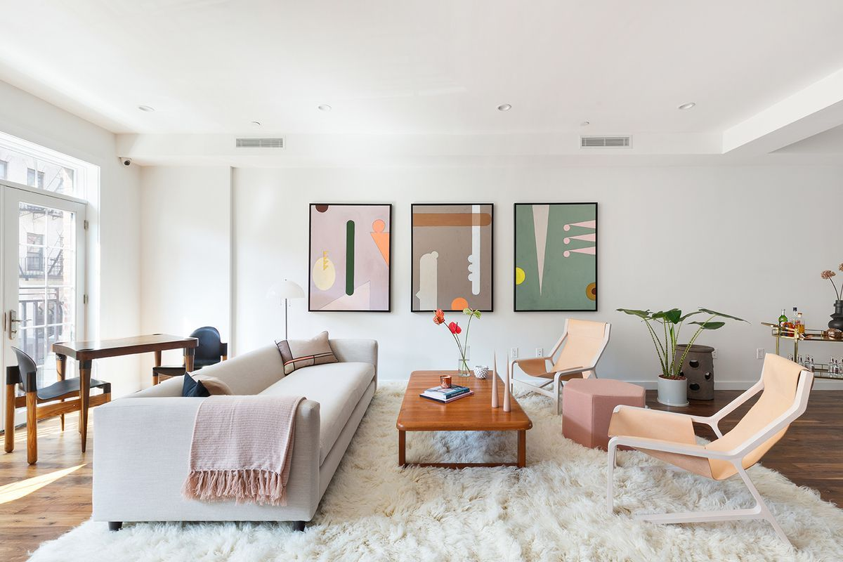 Colorful trio of framed fine art pieces in a light filled living ...