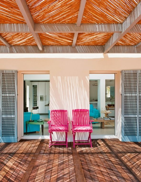 Deck inspiration. Thatched roof protects from the sun while still letting rays shine through. Bright pink chairs liven up the deck.