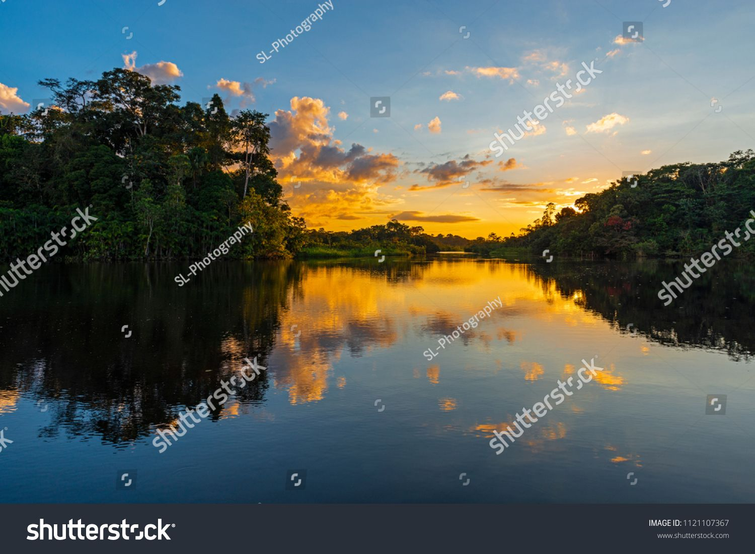 Sunset In The Amazon River Rainforest Basin With A Reflection In A