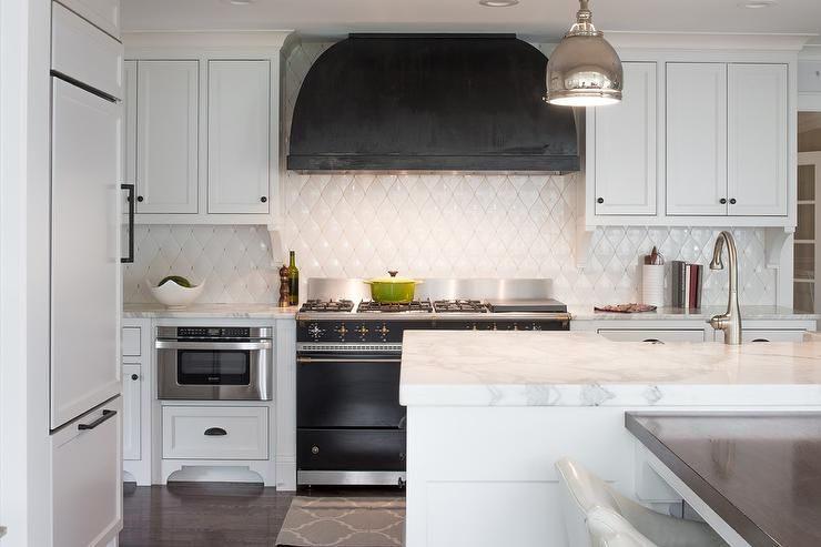 Black Kitchen With Full Wall Of White Marble Tile Black Range Hood With Stainless Stove Dessign Manifest Kitchen Marble White Kitchen Paint Black Kitchens