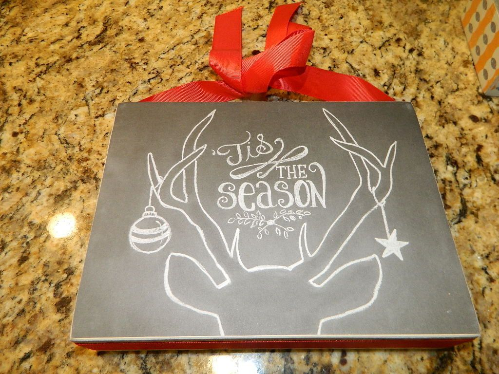 """This is a cute chalkboard style sign of a deer head and antlers with 'Tis The Season between the antlers and a Christmas ball hanging from it. The hanger is a red fabric with a bow. It measures 10"""" X"""