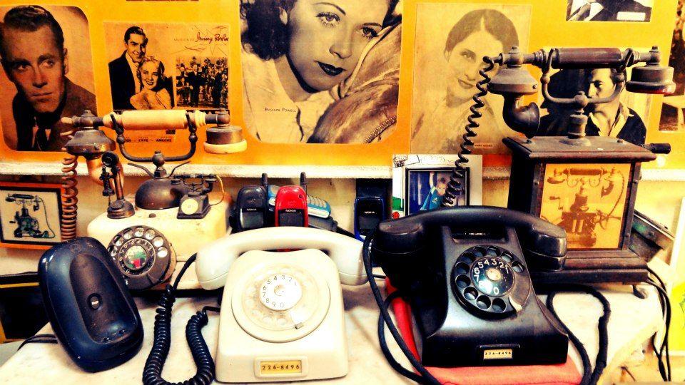 Telefones de várias épocas com fotos de grandes ícones do cinema ao fundo.