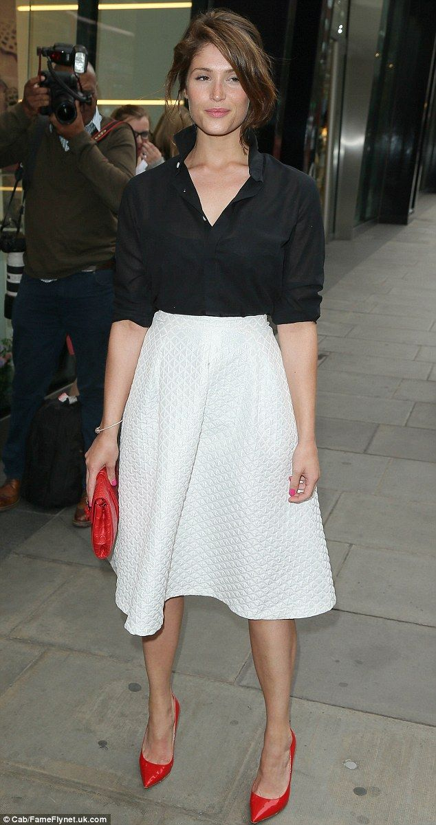 Gemma Arterton looks tanned in a black shirt and white skirt