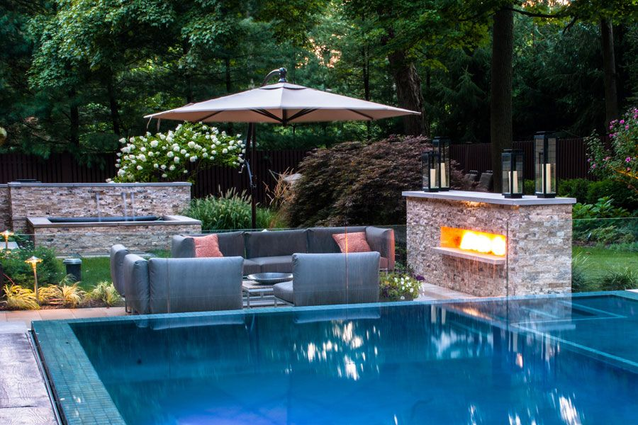 Grey Furniture Front Stone Fireplace And Big Umbrella As Cool Pool ...