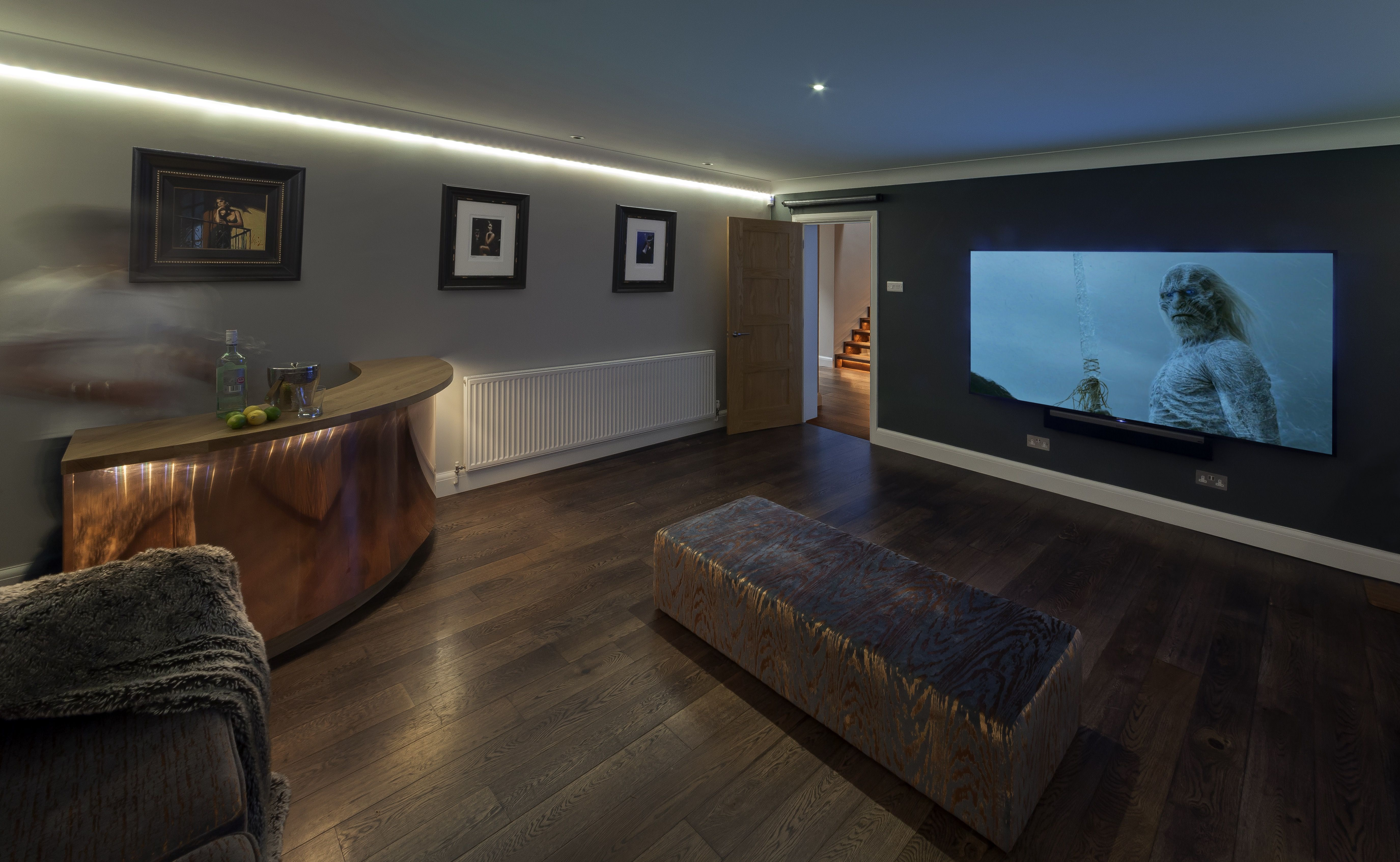 Home cinema room with curved copper fronted bar Caroline