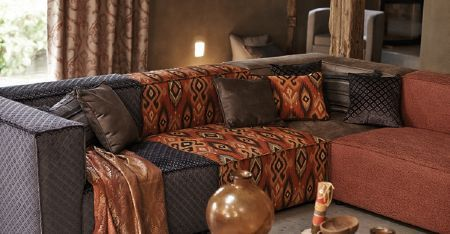 Kobe -  Nomad Fabric Collection - A modular corner sofa including burnt orange, dark brown, midnight blue and orange tribal patterned sections, and cushions