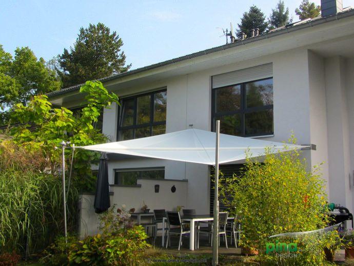 Sonnensegel Elektrisch sonnensegel in manuell aufrollbar über einer terrasse als