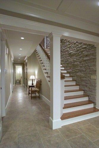 Trappen er vildt flot og elegant. Elsker at den folder sig ud ved foden af den og at der er åbent ud til gangen - det åbner gangen op. Flot at trinene er mørke og resten hvidt Stenvæggen er rigtig flot!   Flot form fliser på gulvet, måske lidt mørkere? Og ikke så broget?  Flot med spot i loftet