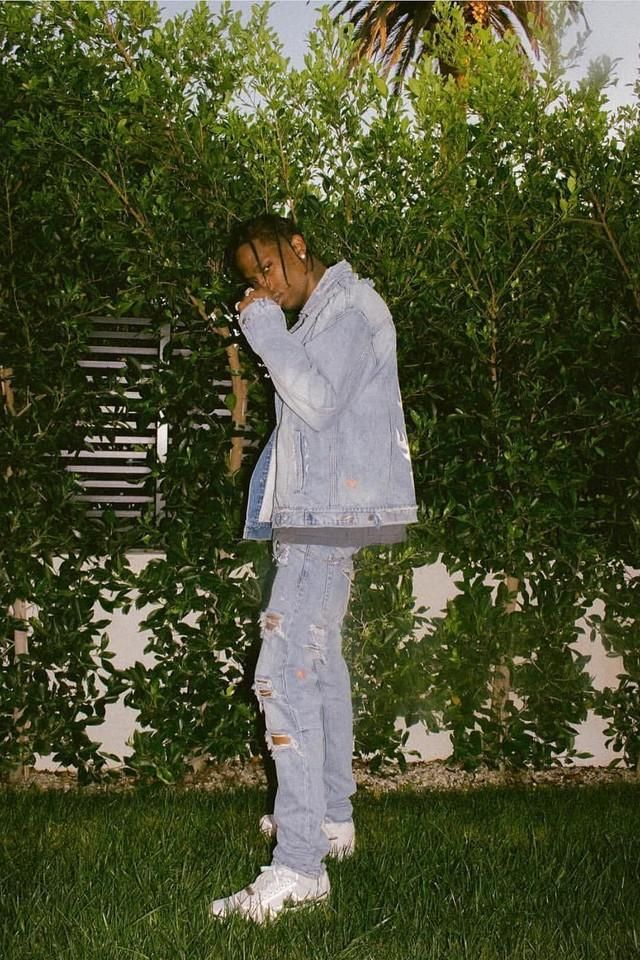 Travis Scott in denim outfit and a pair of white Nike sneakers
