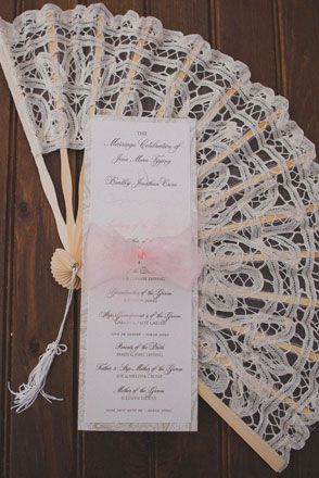 Vintage style lace fan with elegant ivory and pink ceremony card | Photo: Trenholm Photography