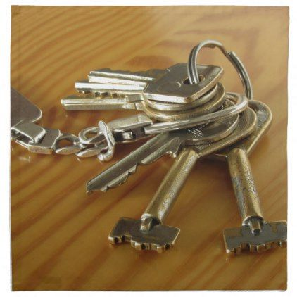 Bunch of worn house keys on wooden table cloth napkin ...
