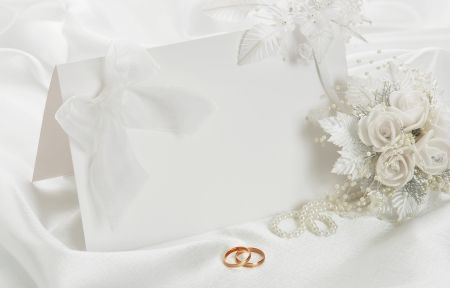 Two gold wedding rings, red rose and card over white satin ...