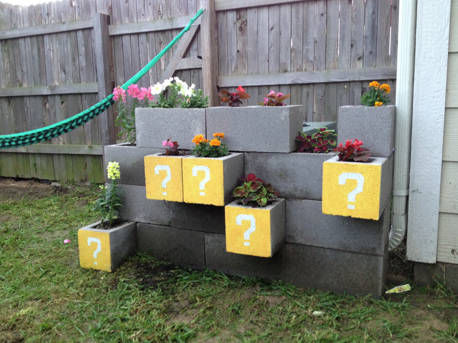Cinder block planter to hide AC unit, painted to look like Mario cubes - Nerdy Block Planter Hide Ac Units, Mario And Planters