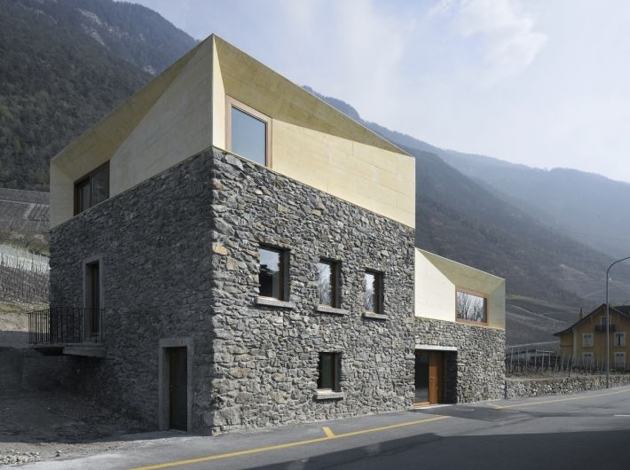 In the Swiss town of Charrat in the canton of Valais, concrete and stone unite as a chronological and material chimera by Clavien Rossier Architects