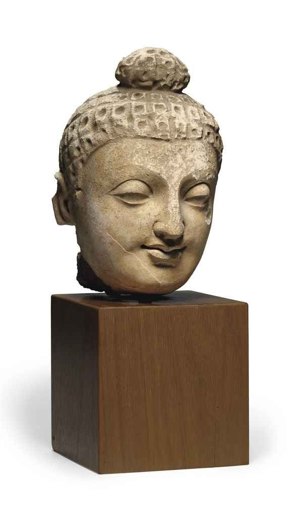 A stucco head of Buddha GANDHARA, 3RD/4TH CENTURY A stucco head of Buddha Gandhara, 3rd/4th century Finely modeled in a serene expression with full lips and heavy-lidded eyes, the hair in neat rectangular rows, with remains of polychromy 7 5/8 in. (19.3 cm.) high