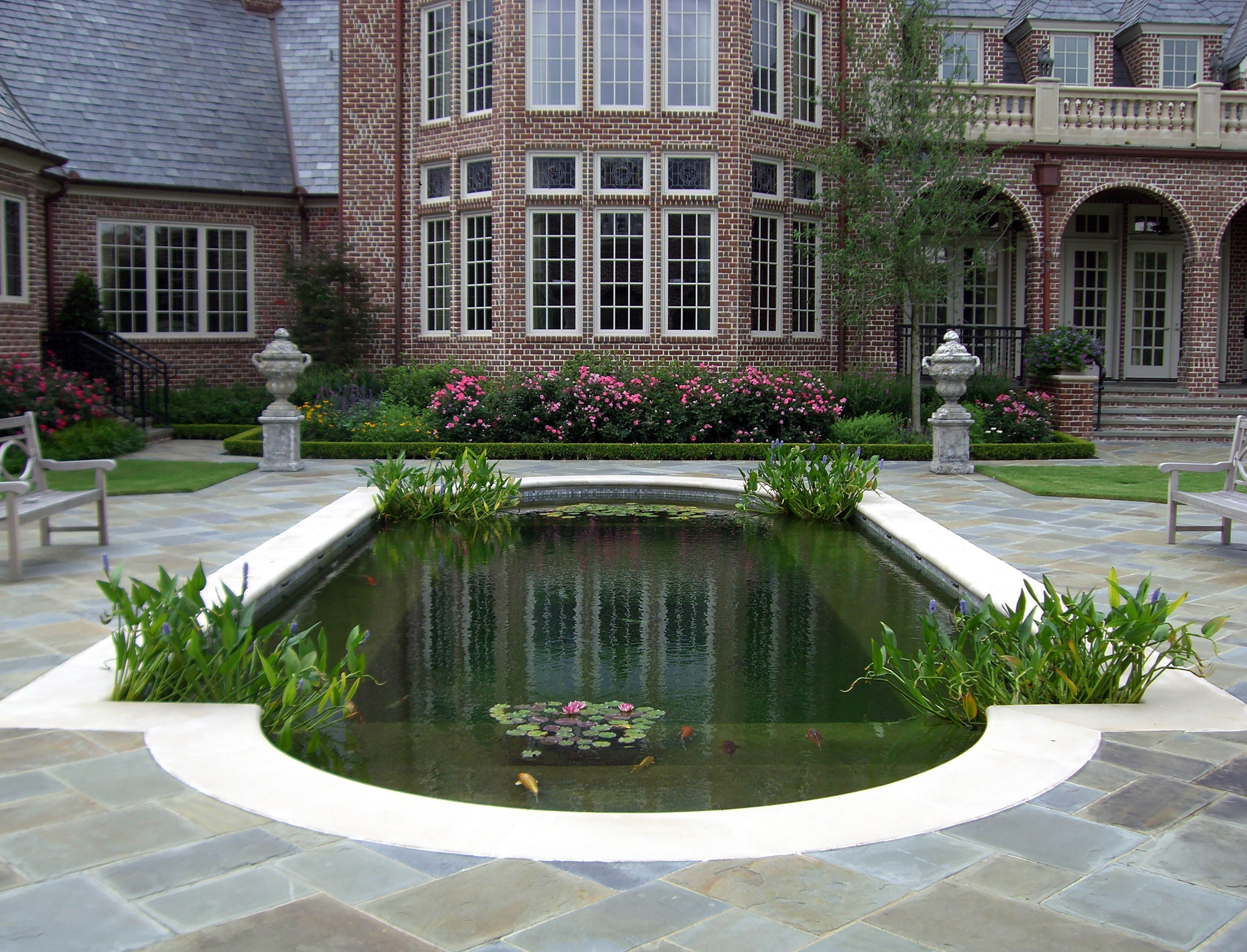 English tudor garden with traditional formal koi pond for Formal koi pond