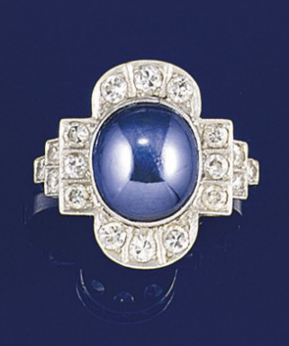 An Art Deco star sapphire and diamond ring  The old brilliant-cut diamond geometrically shaped panel with central oval star sapphire collet and old-cut diamond three stone stepped shoulders, circa 1925.