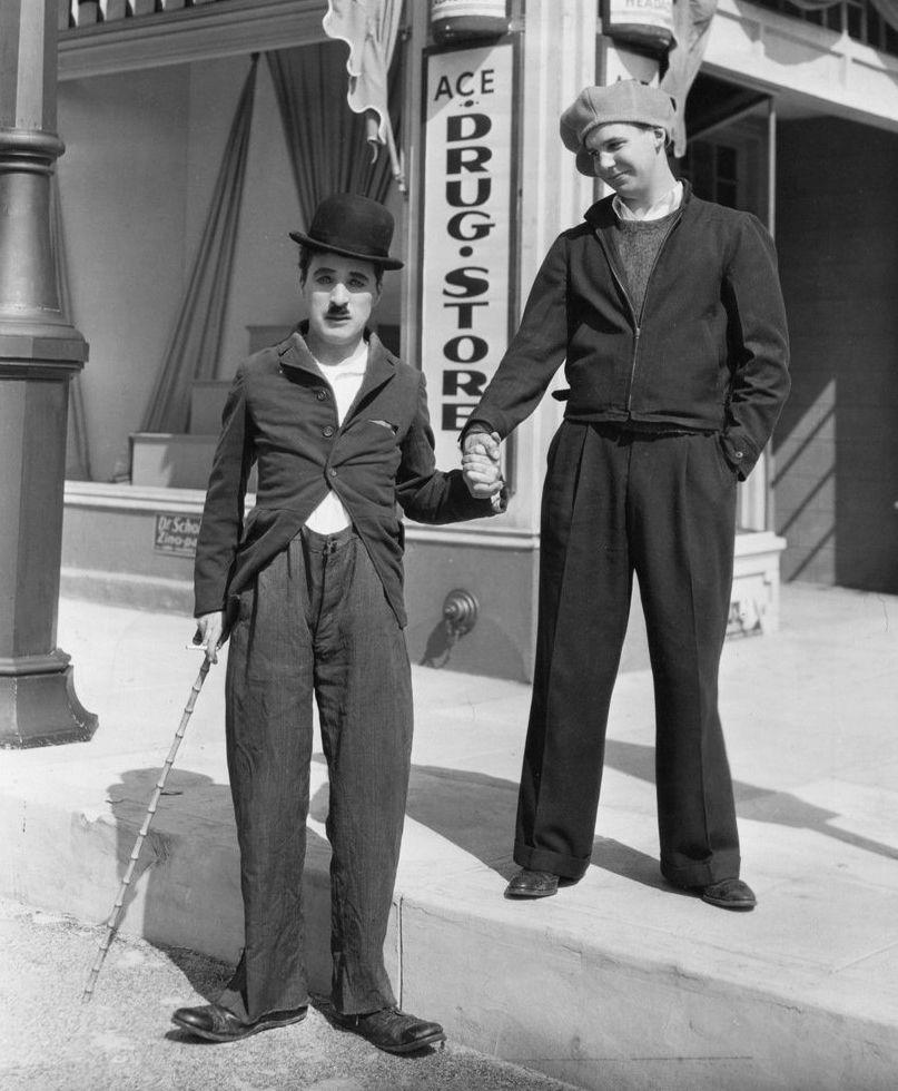 "1935 - Jackie Coogan visits Charlie Chaplin on set of ""Modern Times""."