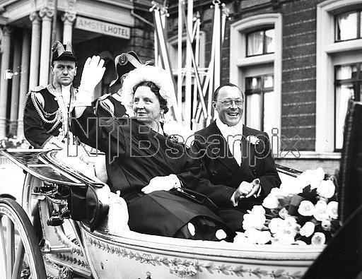 The royal couple celebrating their wedding anniversary, riding a coach through Amsterdam.