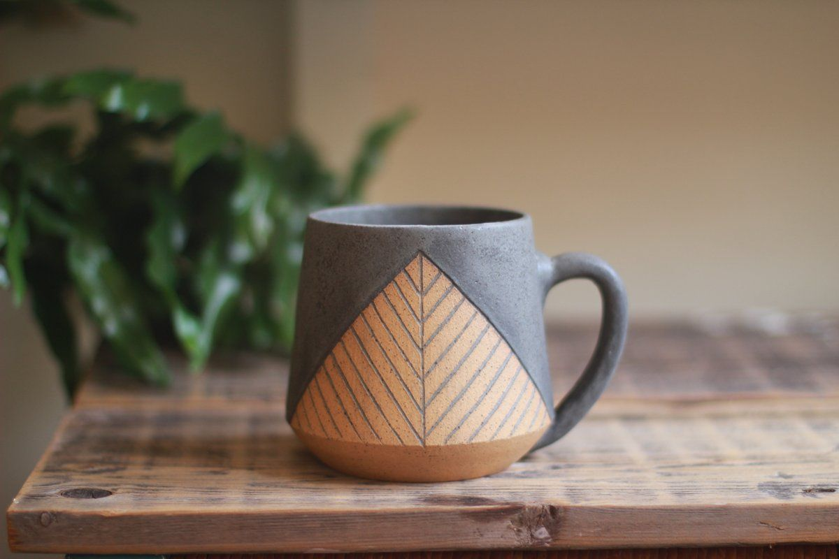 Wheel thrown and hand carved mug featuring a lovely triangular pattern. Glazed in matte charcoal over a speckled clay body. Measures approximately...