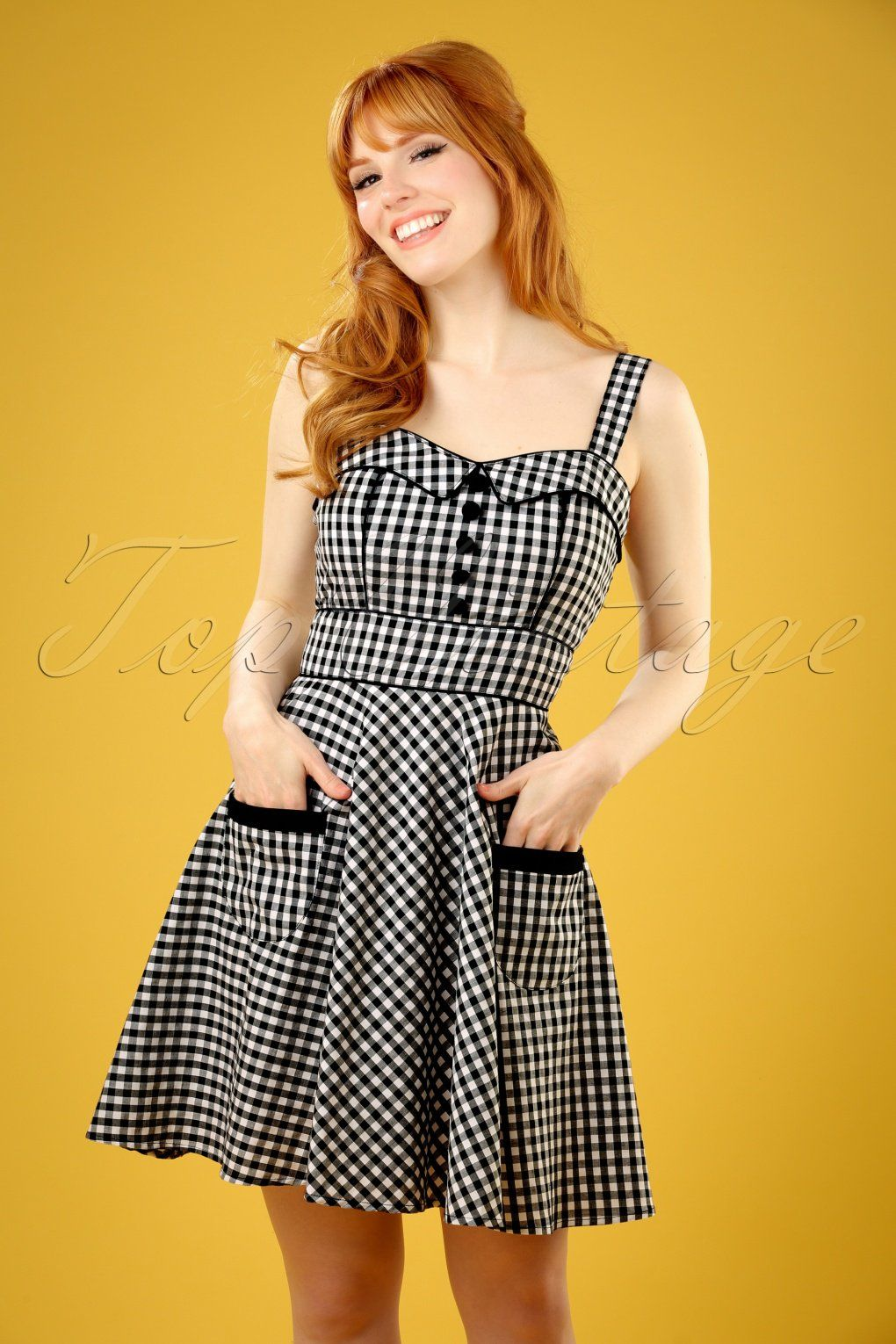 This 50s Bridget Gingham Mini Swing Dressis going to be your new favourite dress!  Why wait for a special occasion? Every day is a good day to wear this beauty! The beautifully fitted top features a subtle sweetheart neckline with typical fifties fold overs, contrasting black faux buttons and two adjustable shoulder straps.The small front pocketsand black piping finish it off perfectly! Made from a cotton blend with a light stretch and playful black/white BB...