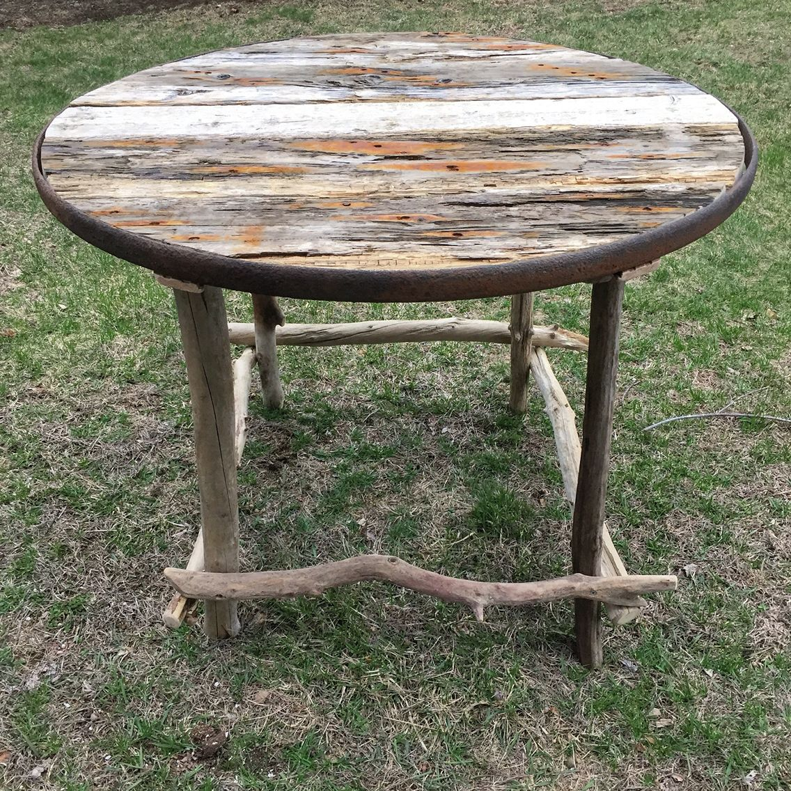 Vintage wagon wheel driftwood table. Available at Ivy Lane in Newburyport MA