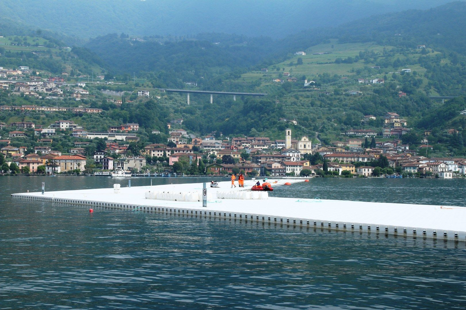 The floating piers designed by Christo and Jeanne-Claude, a system of 220,000 high-density poly-ethylene cubes, covering 100,000 square meter, in an area 100 kilometers east of Milan lake Iseo.