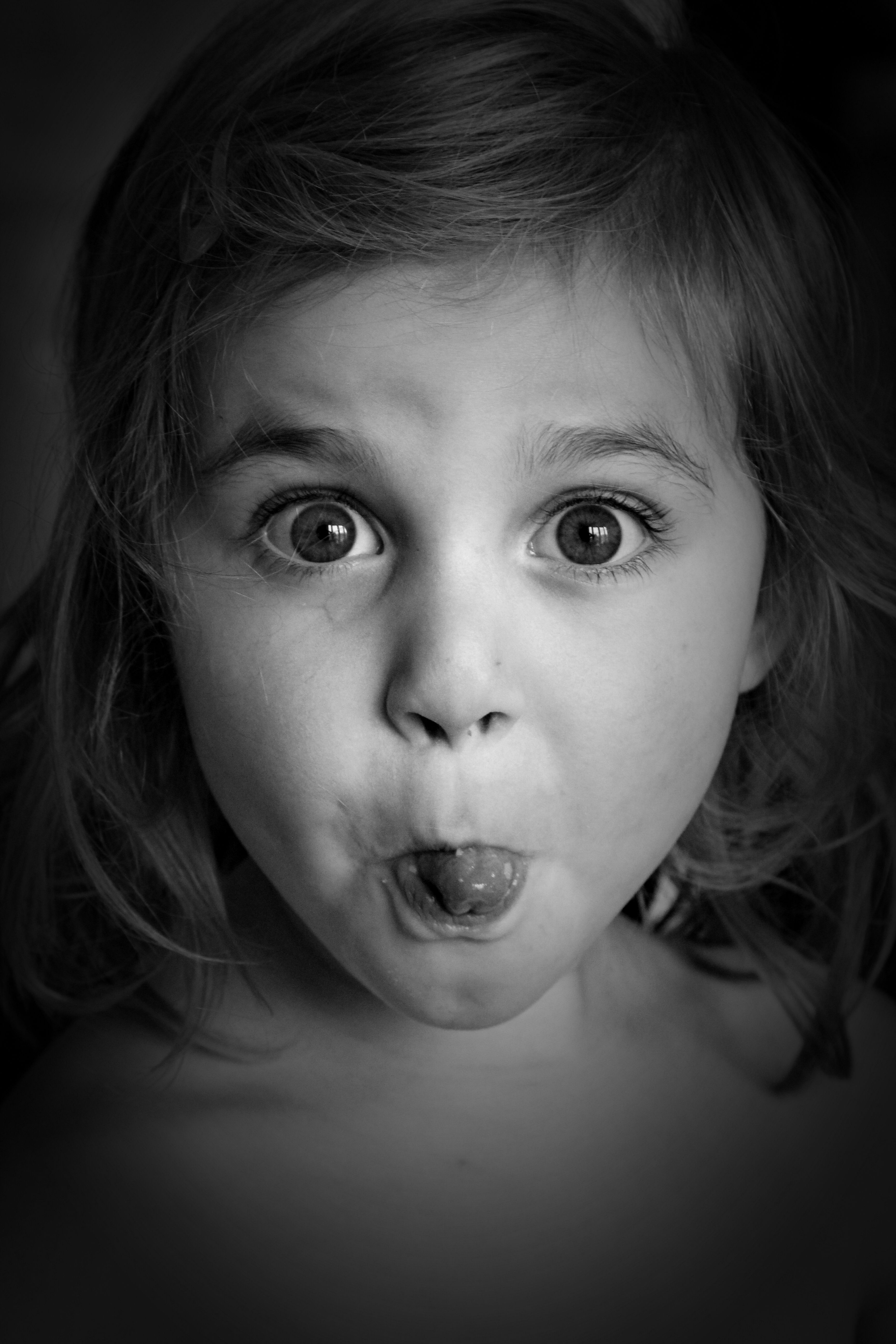 Black and white photograph of girl poking tongue out