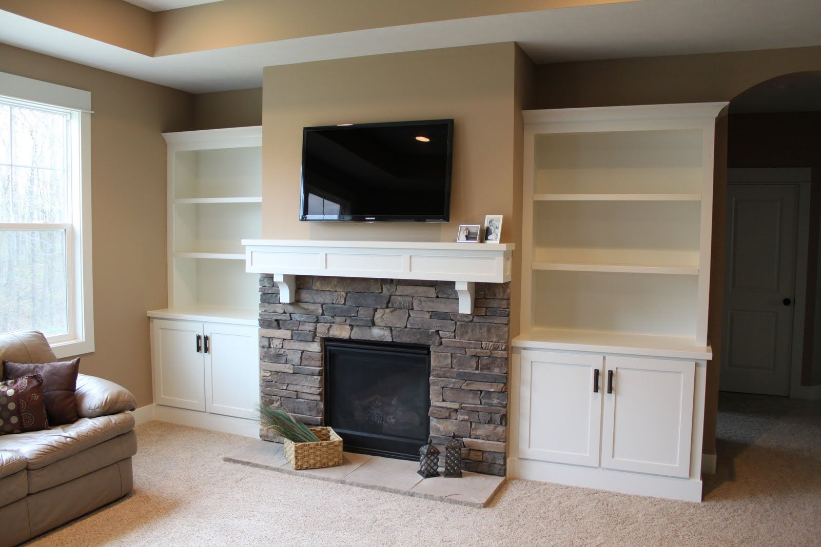 Shelves and cupboards by fireplace TV over fire place ...