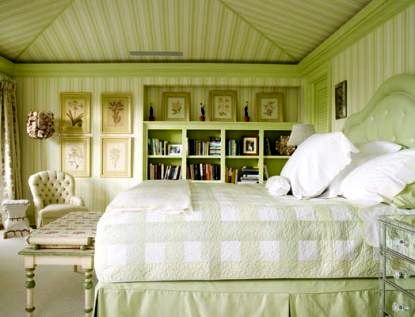 Appropriately celery green bedroom by Celerie Kemble. Adore the striped wall paper that extends up the vaulted ceiling to create a tented effect. This tented look combined with relatively low ceilings, tufted furniture, full drapes, lovely built-ins, and personal effects like books and framed floral prints give such a cozy feel to this space.
