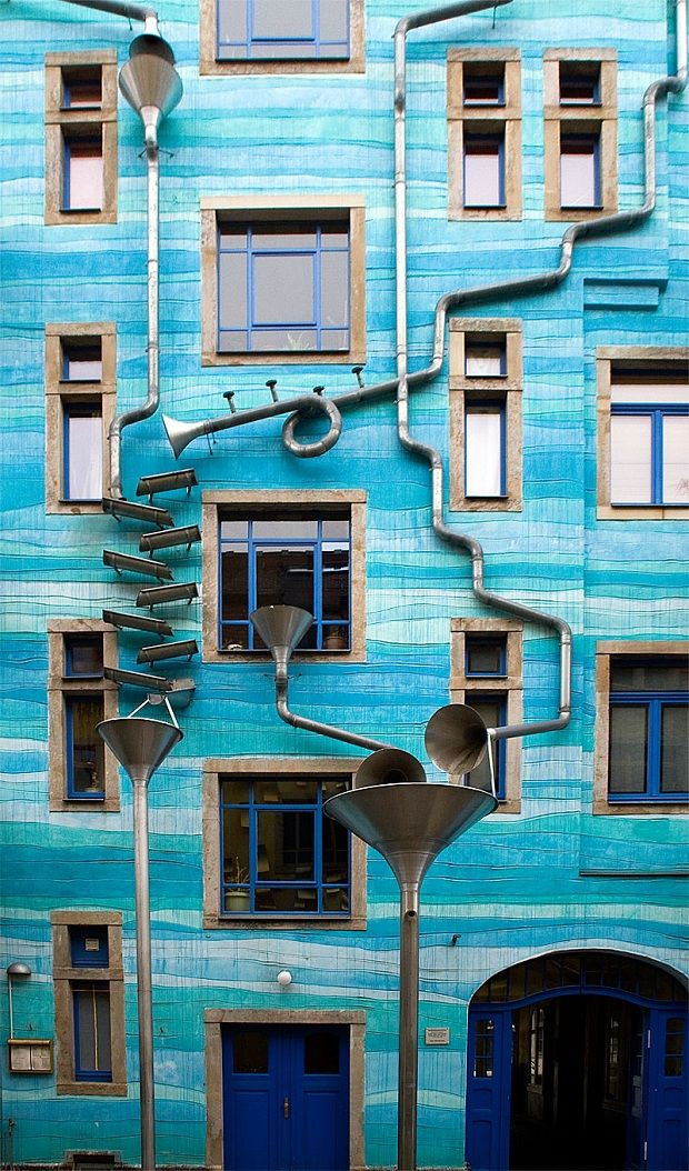A large, multi-story blue building houses the funnel wall attraction designed by three collaborative artists including Christoph Roßner, Annette Paul, and Andre Tempel. The three artists knew that the building needed to have rain gutters, so why not get a bit creative? This system of mousetrap drain and gutters features various sized metal cones that play music when it rains.