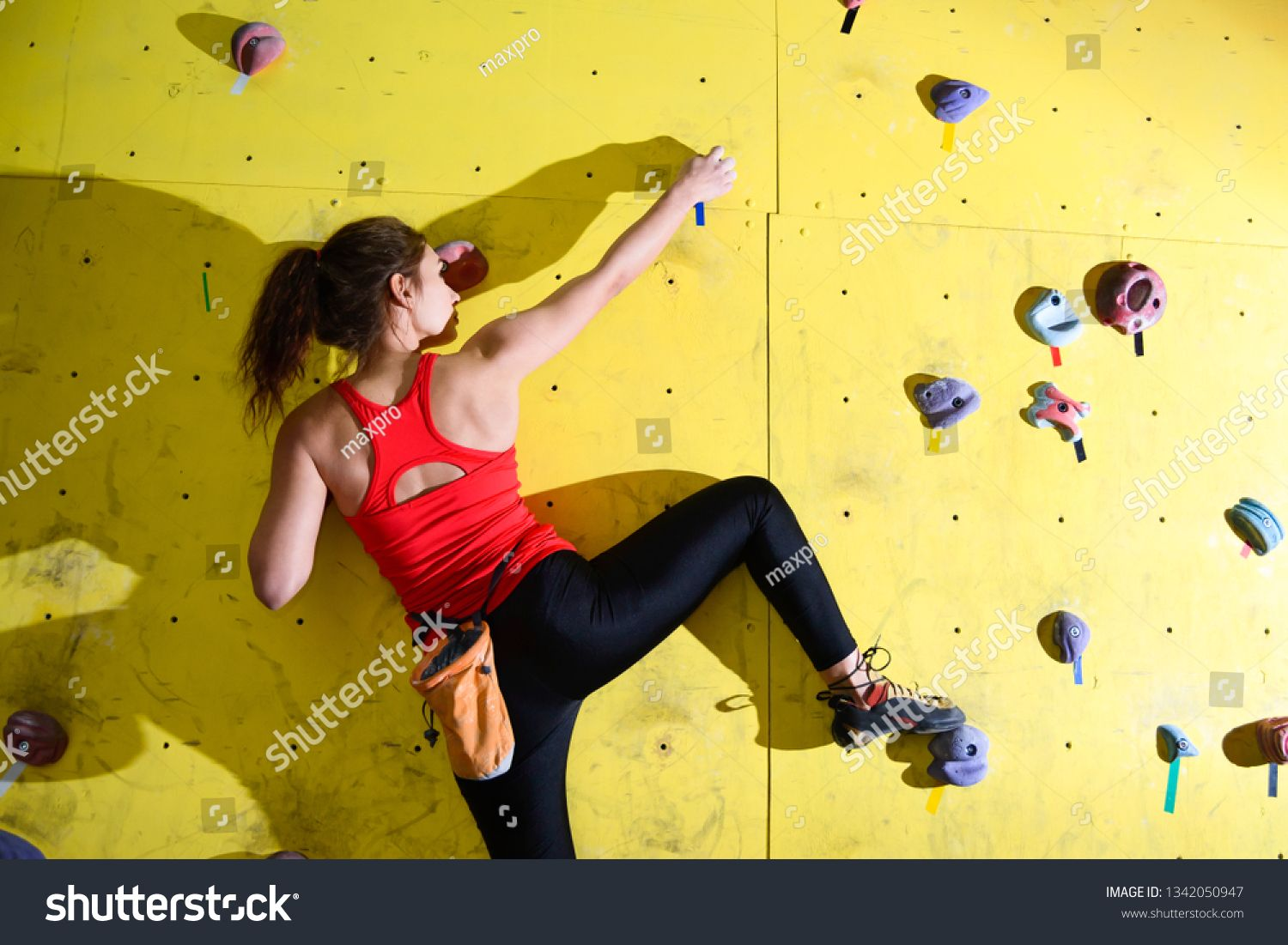 young active woman bouldering on colorful Royalty Free