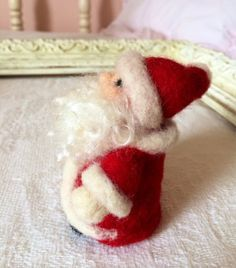 Needle Felted Santa Claus/ Father Christmas by thefeltedcottage  Just in time for the holidays. This adorable tiny NEEDLE FELTED Santa will be a bit of joy to any collection or desktop...He's small enough yet has so much character (you may be tempted to leave him out year round:) Comes with a sweet needle felted santa bag with small candy canes at top♥