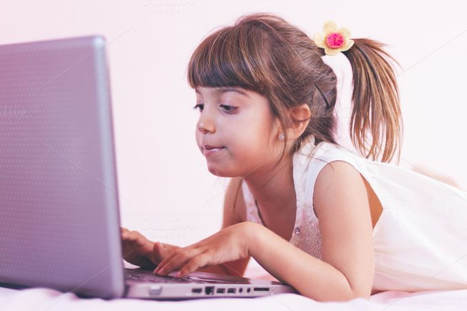 Check out Little girl playing with laptop by OSORIOartist on Creative Market