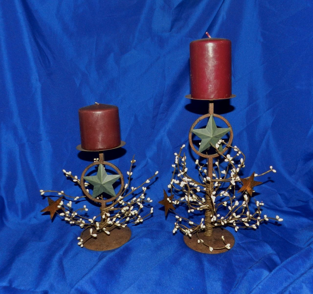Set of primitive rusty star pillar candle holders with white pip