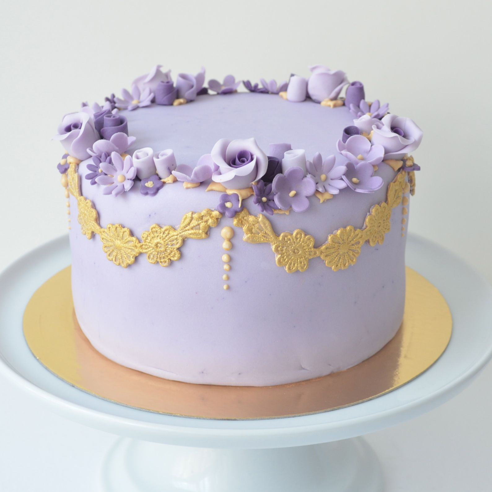 Golden lace with a crown of violet flowers cake Petra cakes