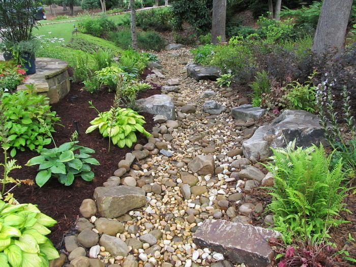 A dry creek bed consisting of various sizes of pebbles for River rock landscaping