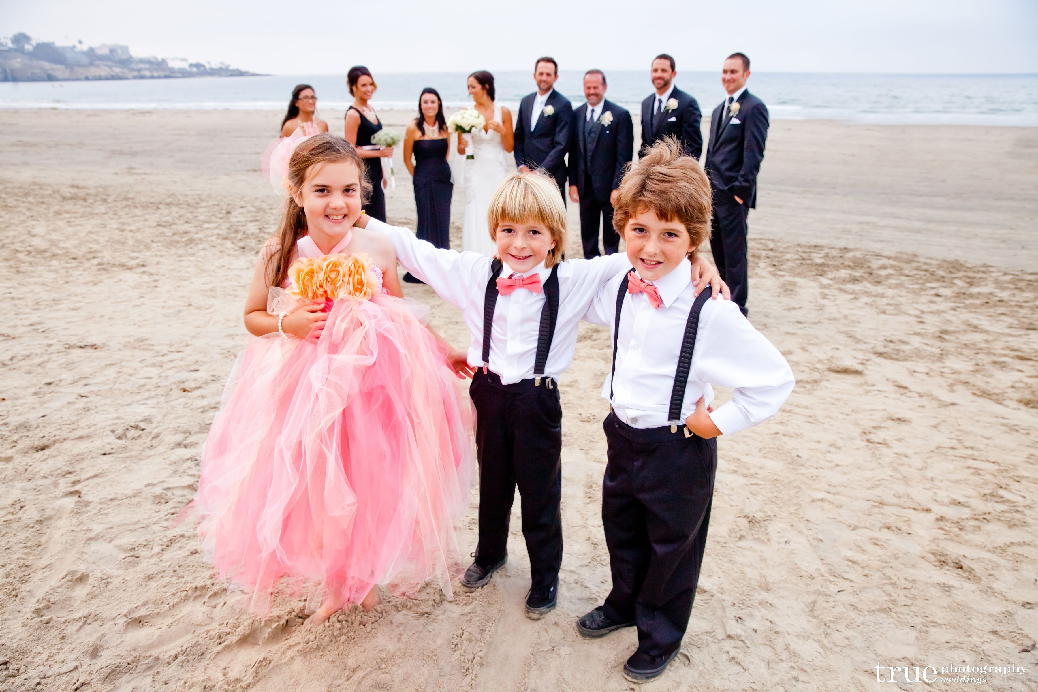 Flower girl in pink with ring bearers and the wedding party on the ...