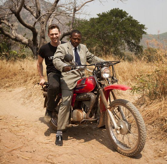 """UNICEF UK Blog. """"Our next stop is the remote village of Loppe. We park up by the road. It's a mile-long walk to the village through the bush. Halfway along the path a distinguished gentleman in an impeccable khaki suit and tie pulls up on a motorcycle and tells me to hop on the back. Riding pillion on the back of a motorcycle through West African countryside under the midday sun delivers a shot of speed and adrenalin. It blows away a few cobwebs. It's great."""""""