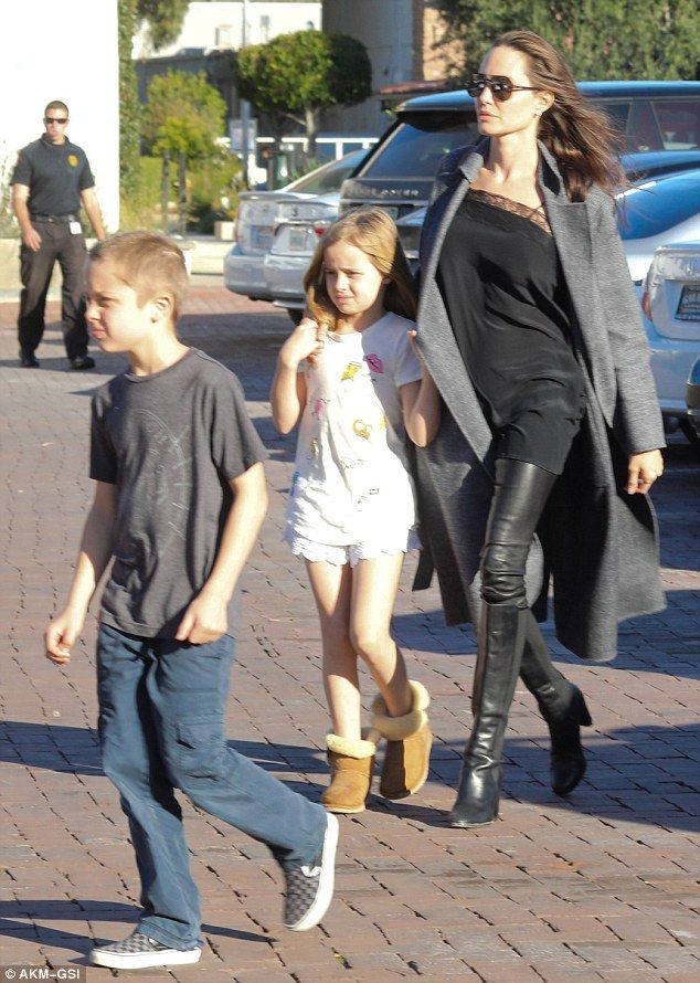 Coordinated ensemble: Angelina looked stunning and stylish in a silky top paired with black leather pants tucked into knee-high black leather boots that emphasized her slim frame