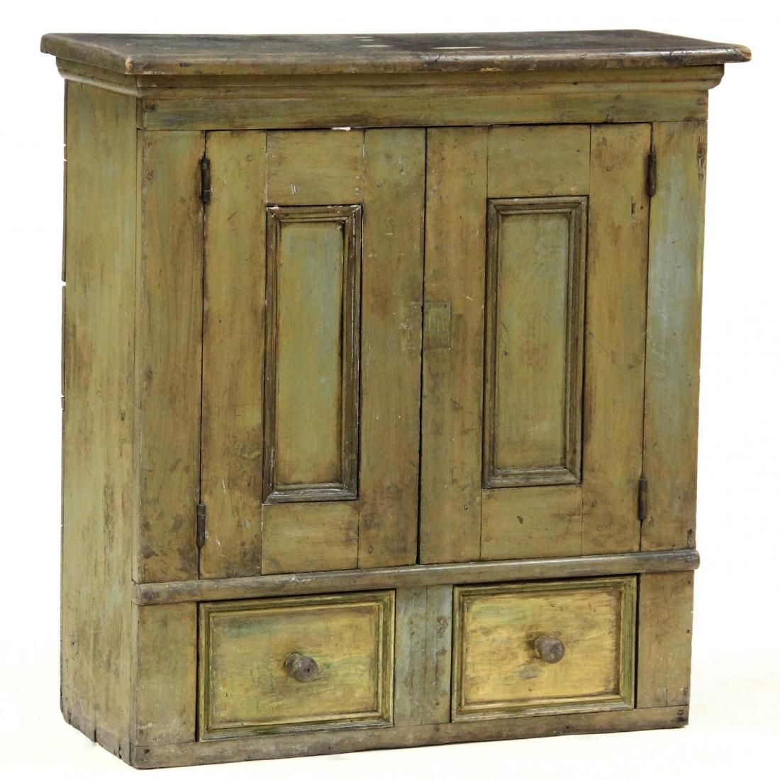 late 19th century, white pine, distressed green painted surface, hinged paneled doors with shelved interior, over two drawers.  34 x 32 x 13 in.  Collection of Carol Charny of New York and Chapel Hill.