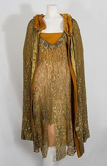 Jeweled metallic lace evening ensemble, c.1925. Made from gold metallic lace in fine condition, the magnificent ensemble has a matchless splendor and brilliance. The lace is embellished with jewel-tone glass beads and faux pearls. The sparkling beads on a golden canvas convey a regal, luxe work of costume art. The intricate, semi-abstract design uses rounded (feminine) motifs, including the ancient tear-drop boteh. The dress comes with a burnt orange silk chiffon slip. @Deidré Wallace