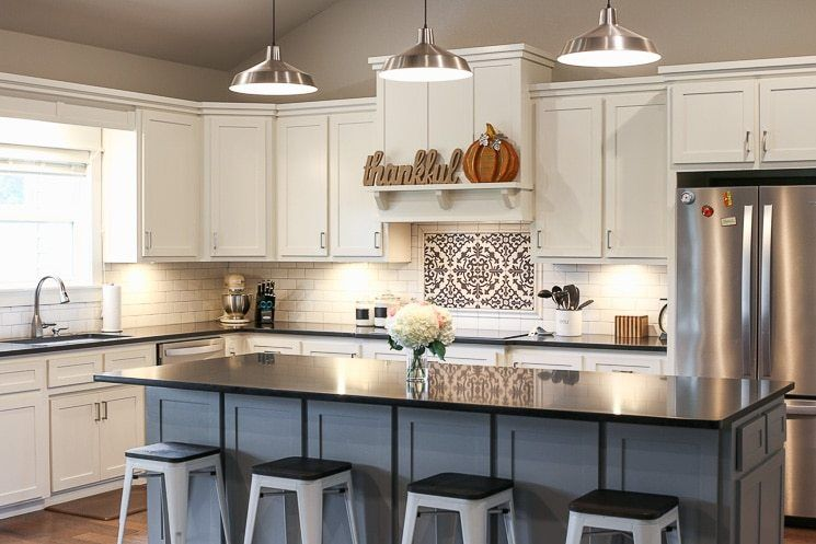 A Picture Of A Kitchen With White Cabinets Black Countertops And A Gray Island Black Countertops Replacing Kitchen Countertops New Kitchen Cabinets