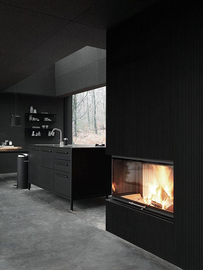Moderne schwarze Küche und ein offener Kamin als gemütliches ...