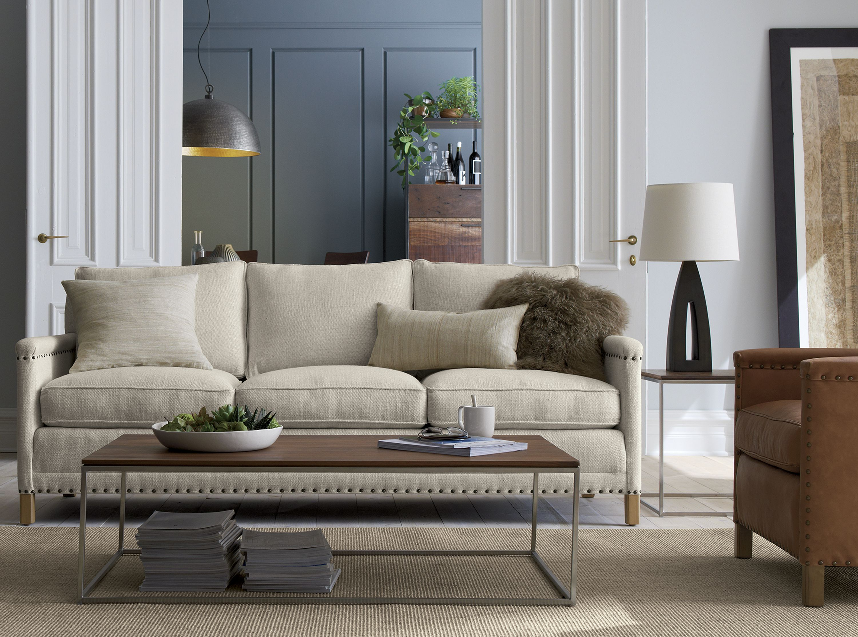 Our Trevor collection inherits the fine tradition of American craftsmanship with a clean modern style all its own. Impeccably tailored in an elegant spun-linen fabric, Trevor is tucked and tacked with natural brass nailheads, each precisely placed by hand. The sofa's comfort level is truly gold-standard, crafted with the support of eight-way, hand-tied springs, seat cushions lofted with down.