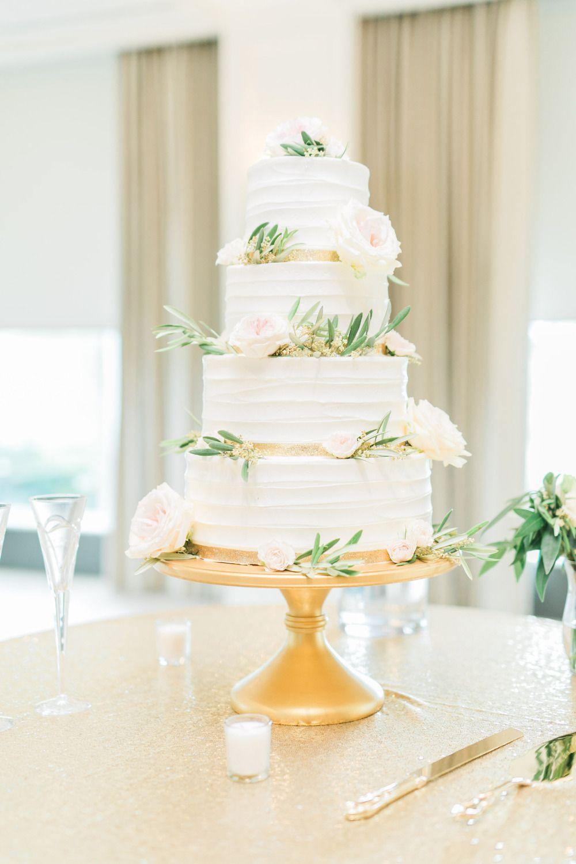 white wedding cake with gold ribbon