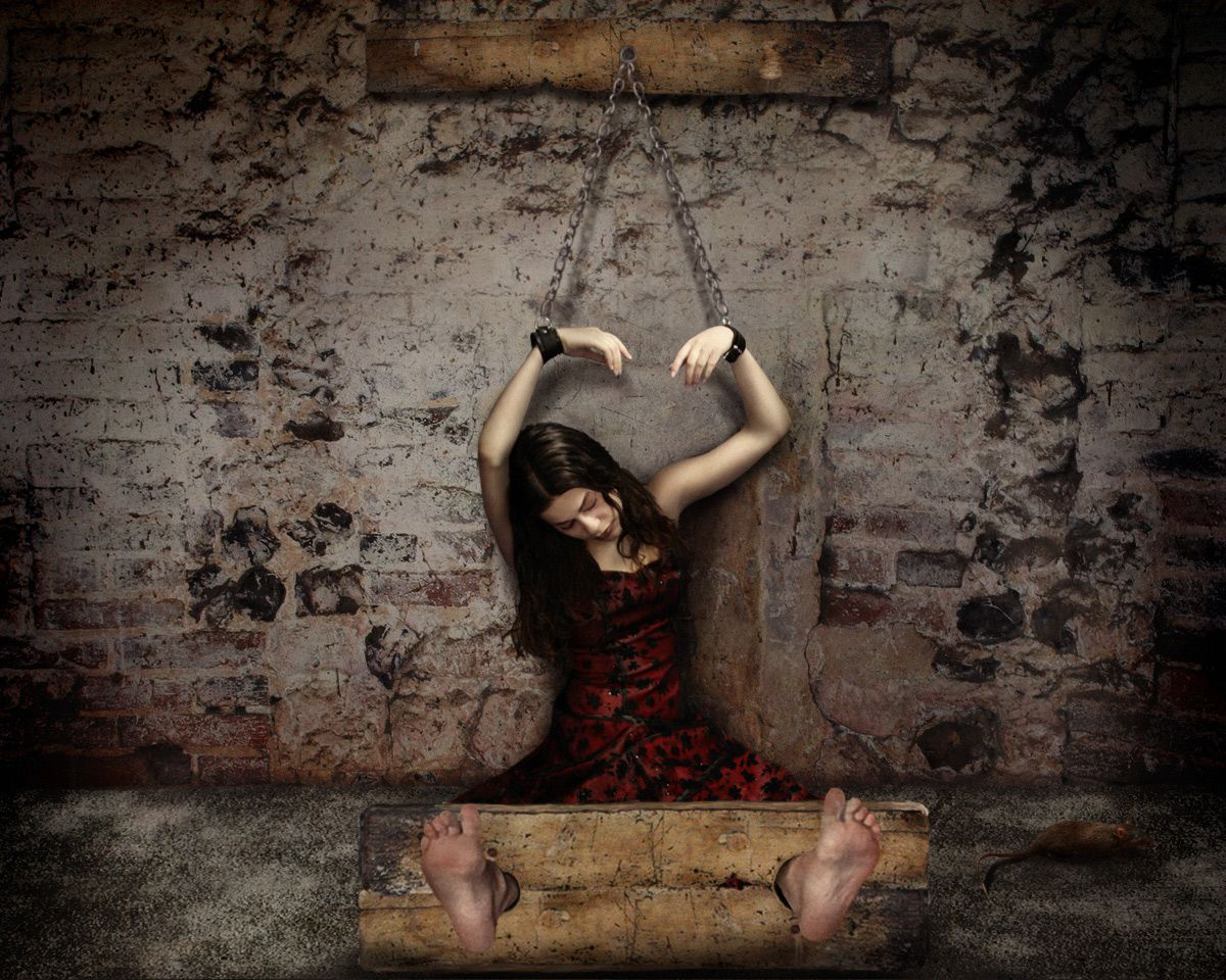 Nude girl is chained to the wall