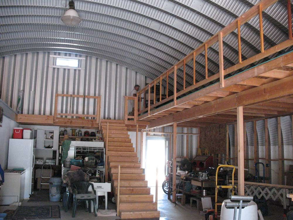 Two tiered garage inside of an s-style steel building | Quonet hut on