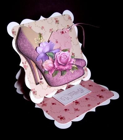 Stunning Shoes Belle Roses 8 Step Decoupage Sheet on Craftsuprint designed by Anne Lever - made by Dianne Jackson - I decoupaged this beautiful topper using sticky pads following the step by step and mounted onto a shaped easel card. I matted the easel with co-ordinating rose design backing paper using a light shade on the main part and a darker shade on the base. I cut a tag from the dark shade and mounted so that it was peeping from the shoe. I threaded pink ribbon and pearls through the…